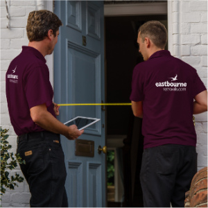 removal men measuring a front door for a house move